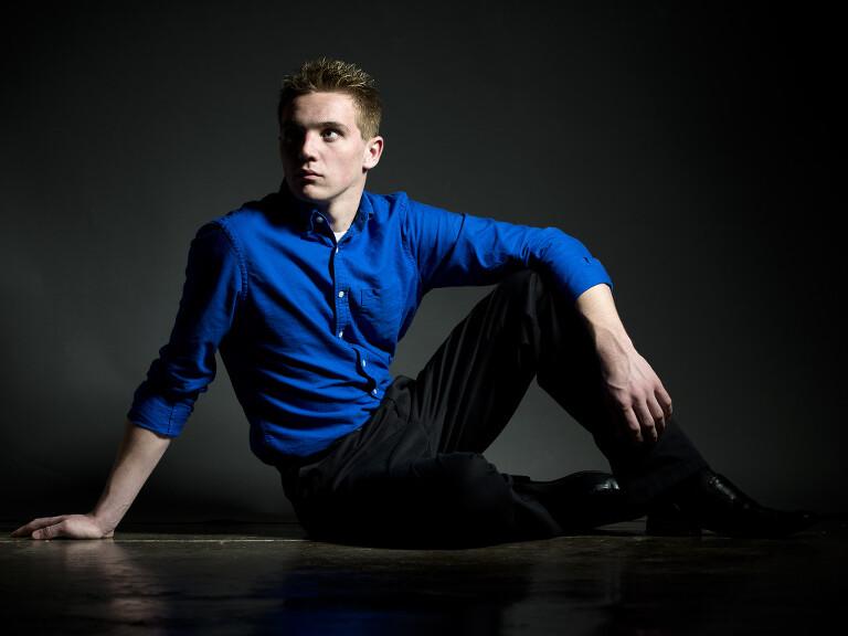 senior portrait photography guy sitting on studio floor