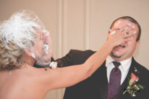 Bride and groom with cake in face