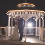 Bride and groom under gazebo at night