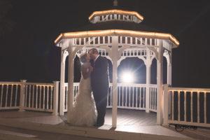 Bride and groom under gazebo at night