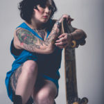 Tattooed woman with skateboard