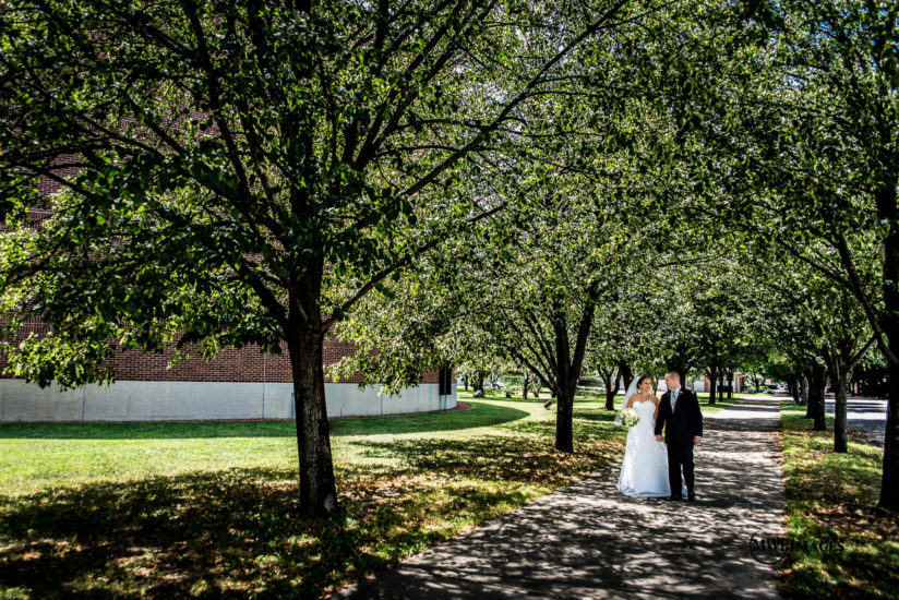 bride and groom walking along tree covered sidewalk