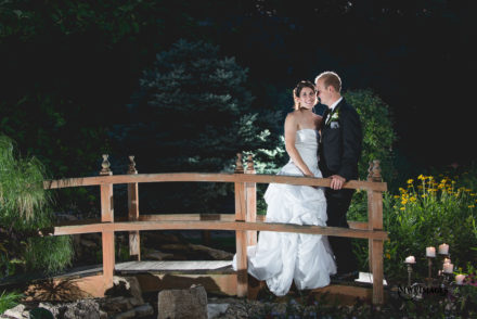 bride and groom on bridge at night