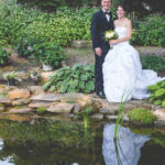 bride and groom beside a pond