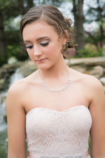 high school senior girl poses for prom photo