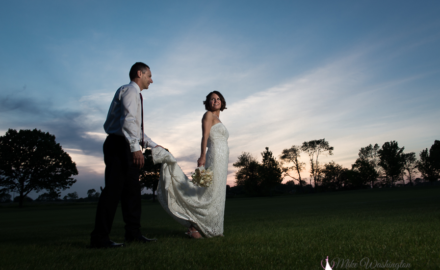 bride and groom with sun setting in background