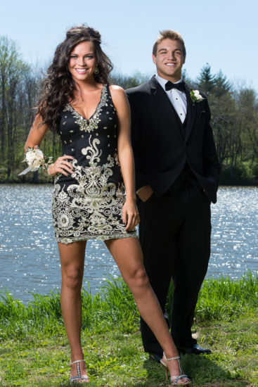 couple poses for their high school prom photo