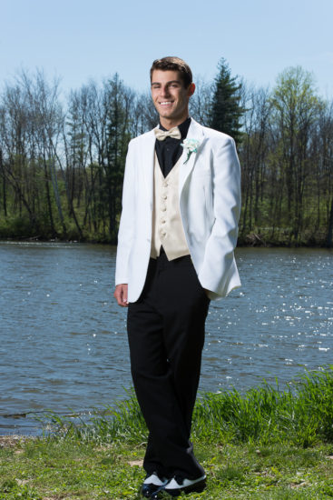 high school senior boy poses for prom photo