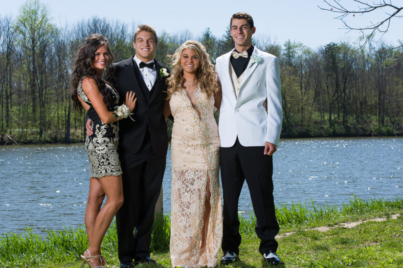 couples pose for their high school prom photo